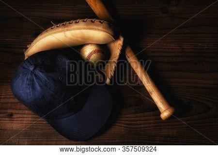 High angle shot of a catchers glove with used baseball, a wood bat and baseball cap.