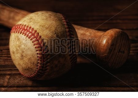 Closeup of an old baseball and wood bat on a rustic wooden table.