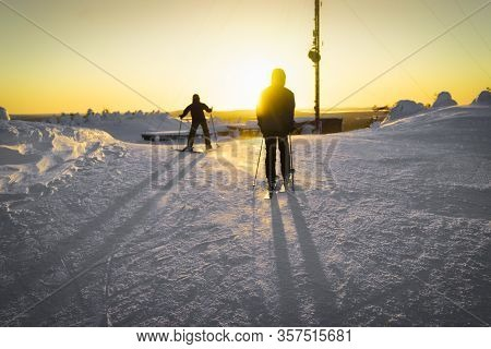 Two Skiers Standing On The Top Of The Mountain, Ready To Ride Down The Hill