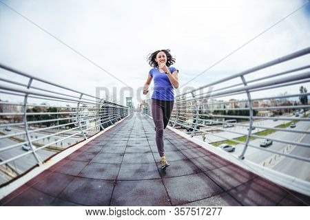 A Woman Runs Across The Bridge Over The Road. Running Training In The City. Girl Trains Endurance. J
