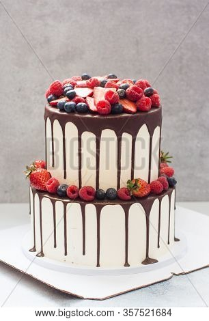 A Three-tiered White Wedding Cake Decorated With Fresh Bright Berries And Melted Chocolate On Grey B