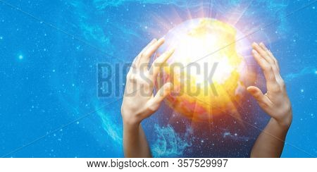 Two Womens Hands Conjure A Glowing Ball On A Blue Starry Background. The Concept Of Paranormal Abili