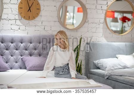 Blonde Woman With Jewelry On Neck Sitting On The Bed.