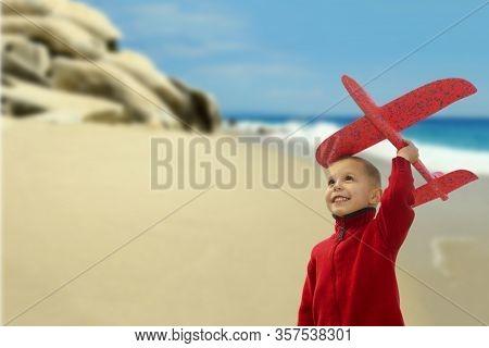Cute Boy Plays With Airplane Near The Sea