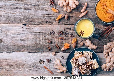 Healthy Vegan Turmeric Latte Or Golden Milk, Turmeric Root, Ginger Powder, Black Pepper Over Wooden