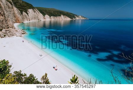 Summer Vacation Holiday. Fteri Beach Lagoon With Rocky Coastline, Kefalonia, Greece. Tourists Under