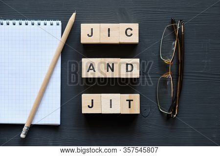 Modern Business Buzzword - Jic And Jit. Top View On Glasses And Notepad With Wooden Blocks. Close Up