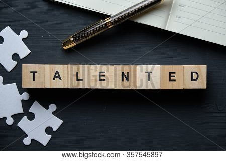 Modern Business Buzzword - Talented. Top View On Puzzle And Notepad With Wooden Blocks. Close Up. To
