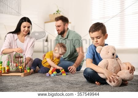 Unhappy Little Boy Feeling Jealous While Parents Spending Time With His Baby Brother At Home