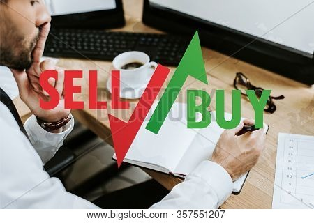 Cropped View Of Pensive Bi-racial Trader Sitting At Table And Writing In Notebook Near Sell And Buy