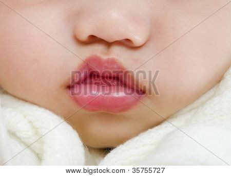 Close up pink lips of a sleeping baby boy with tongue sticking out