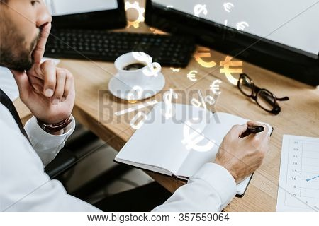 Cropped View Of Pensive Bi-racial Trader Sitting At Table And Writing In Notebook Near Money Signs