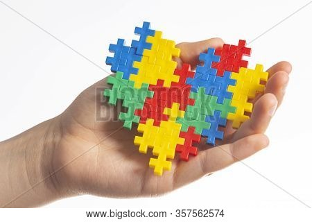 World Autism Awareness Day Concept. Child Hands Holding Colorful Puzzle Heart On White Background