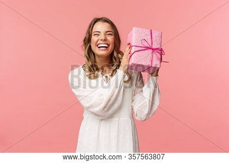 Holidays, Celebration And Women Concept. Portrait Of Happy Charismatic Blond Girl Shaking Gift Box W