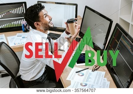 Happy Bi-racial Trader Holding Paper Cup And Sitting Near Computers And Sell, Buy Letters