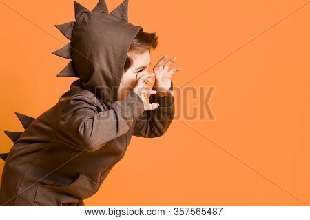 Little Brunet Boy In Brown Dino Hoodie With Hood. He Is Growling And Scaring You By His Hands, Posin