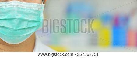 Portrait Of Young Female Doctor Wear Mask On Many Medicine Shelf Background. Coronavirus (covid-19)c
