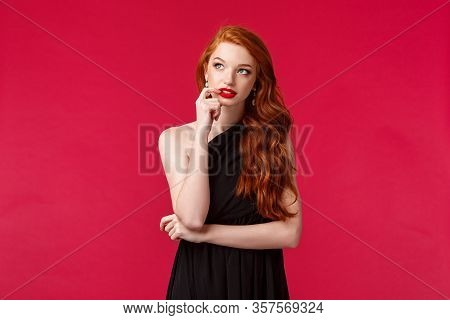 Portrait Of Thoughtful Creative Young Redhead Elegant Woman With Ginger Hair In Black Dress, Biting