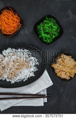 Rice With Sauce On White Napkin, Korean Carrots, Soy Asparagus And Chuka On Black Background Top Vie