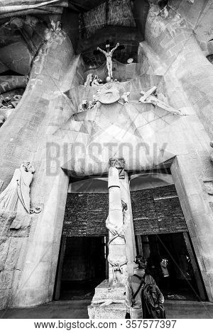 Barcelona, Spain - Feb 6, 2014: Young Man Stands At Entrance  Of La Sagrada Familia, The Cathedral D