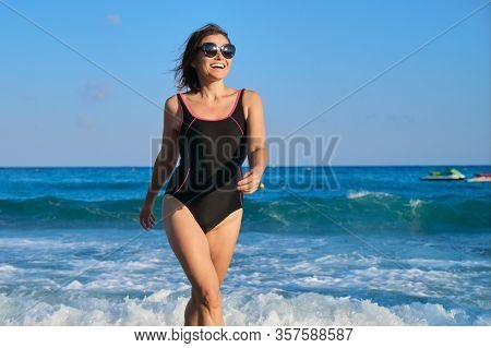 Mature Smiling Woman In Swimsuit With Sunglasses Walking Along Beach. Beauty, Health, Body, Relaxati