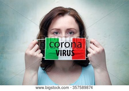 Studio portrait of a woman in a mask on a gray background. ?oronavirus epidemic in Italy.