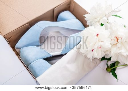 Female Blue Wedding Shoes In Box With White Peonies Flowers On White Background. Present For Mothers