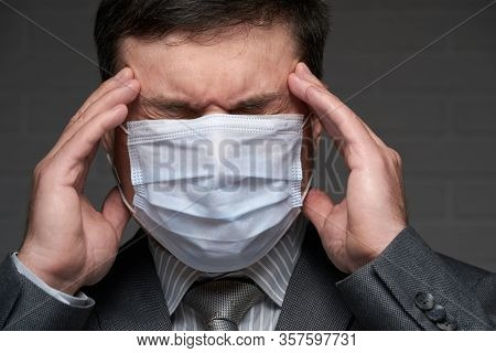 infected man has a headache and symptoms of the disease, he touches his forehead with his hand, has a protective face mask - healthcare and medicine concept