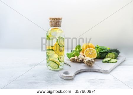 Detox Sassy Water With Lemon, Cucumber, Mint. A Glass Bottle Of Clean, Cool And Fresh Drink Stands O