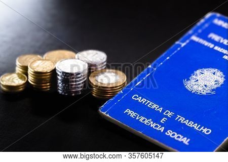 Old Work Card From Brazil, Old And Handled Document. Beside Real Coins, Brazilian Money. Concept Of