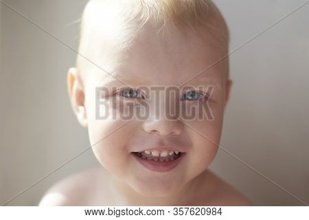 Portrait Of A Happy Smiling Two Year Old Boy On White Background, Blue-eyed, Fair-haired Child.