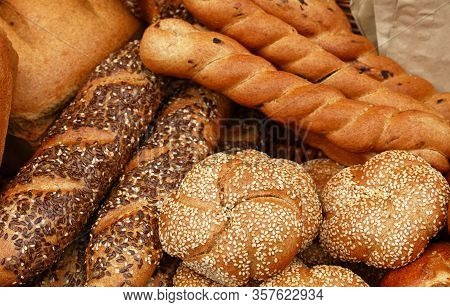 Close Up Several Assorted Fresh Wheat Bread Buns, Loaves And Baguettes On Retail Display Of Bakery S