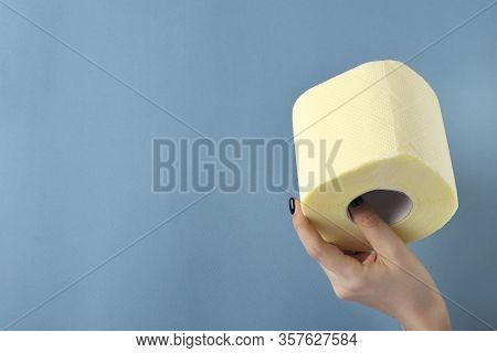 Toilet Paper Roll In A Female Hand On Blue With Space For Text, Covid-19 Pandemic, Deficit, Increase