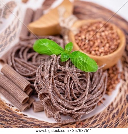 Brown Raw Buckwheat Pasta, Noodles, Buckwheat Groats And Basil Leaves. Gluten Free Concept
