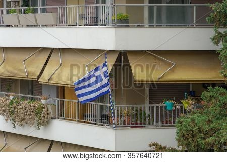 Greek Flag Waving On Balcony For A National Celebration. Blue And White Greek Flag With Cross Outsid