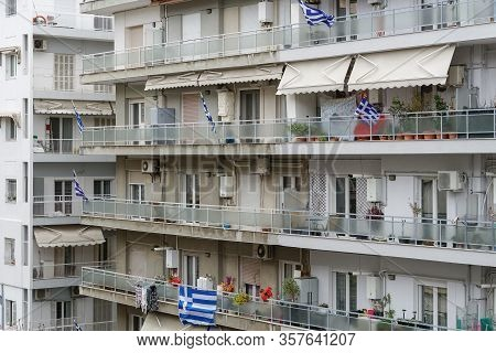 Greek Flags Waving On Balconies For A National Celebration. Blue And White Greek Flags With Cross Ou