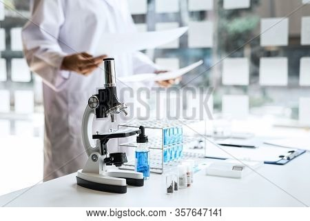 Biochemistry Laboratory Research, Chemist Is Analyzing Sample In Laboratory With Microscope Equipmen