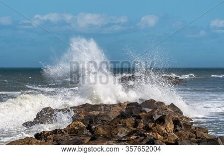 Waves Breaking Over A Rock Jetty Wall.