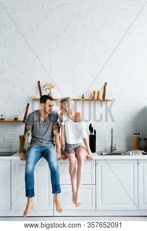 Tattooed Couple Smiling At Each Other While Sitting On Kitchen Worktop