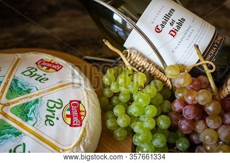 Cheese Brie With Bottle Of Chardonnay Of Casillero Del Diablo With Bunch Of Grapes On The Table