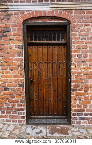 Old Vintage Wooden Door With Brick Archway. Front Door, Double Brown Front Door With A Secured Front