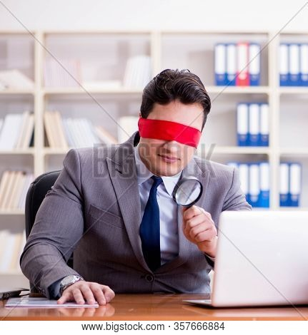 Blindfold businessman sitting at desk in office