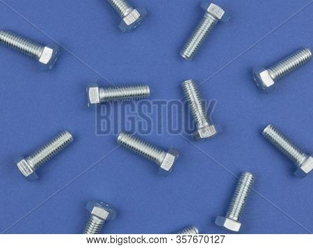 Bolts Closeup On Blue Background. The View From The Top. Fasteners.