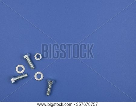 Bolts, Nuts And Pucks  For Fastening On A Blue Background. The View From The Top.