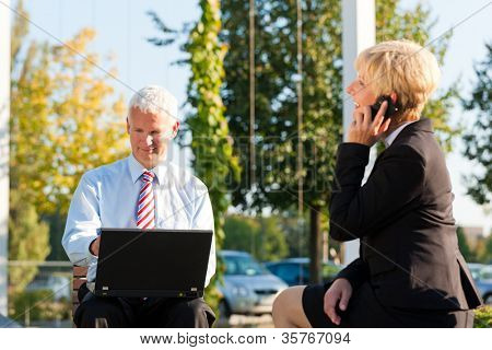 Business people working outdoors - he is working with laptop, she is calling someone on phone