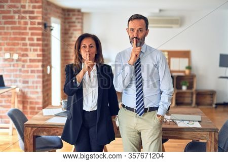 Two middle age business workers standing working together in a meeting at the office asking to be quiet with finger on lips. Silence and secret concept.