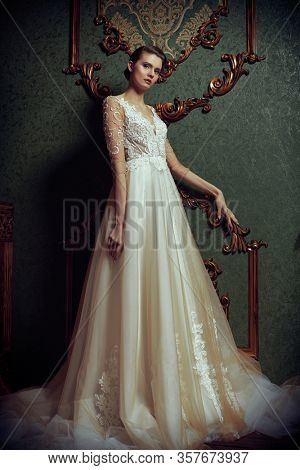 Full length portrait of a magnificent young bride in elegant white long dress. Luxurious dark apartments.  Wedding fashion.