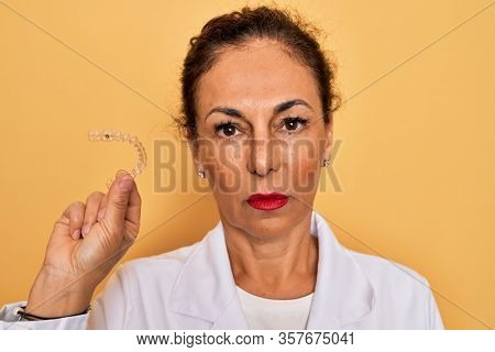 Middle age senior dentist woman holding clear aligner for teeth correction with a confident expression on smart face thinking serious