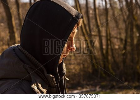 Horizontal Portrait Of A Teenage Boy In A Black Hood, Partially Illuminated By The Sun