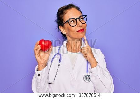 Middle age senior cardiologist doctor woman holding red heart over purple background serious face thinking about question, very confused idea
